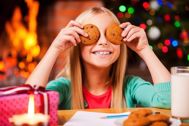 Świąteczna zabawa. śliczna mała dziewczynka zakrywa oczy ciasteczkami i uśmiecha się siedząc przy stole z choinką i kominkiem w tle