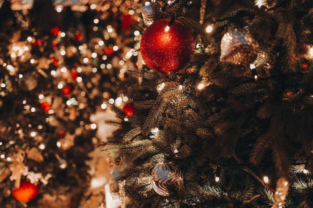 Świąteczna zabawka czerwona piłka wisząca na choince ze złotymi świątecznymi światłami bokeh na tle