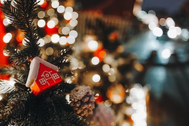 Świąteczna zabawka czerwony dom wiszący na choince ze złotymi świątecznymi światłami na tle