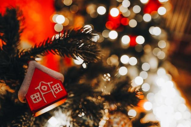 Świąteczna zabawka malutki czerwony domek wiszący na choince z rozmytymi złotymi świątecznymi światłami