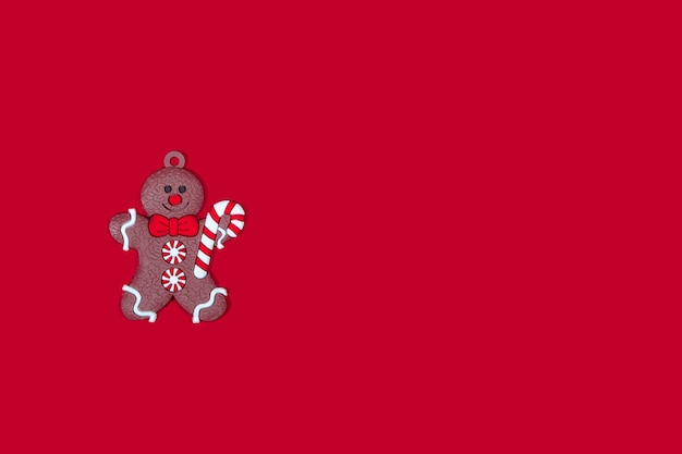 Świąteczna zabawka na drzewie piernikowy człowiek z cukierkami w dłoniach na czerwonym tle