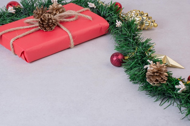Świąteczna zabawka szyszka z czerwonym pudełkiem na szarym stole.