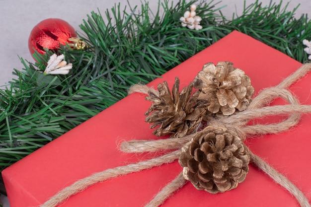 Świąteczna zabawka w kształcie szyszki z czerwonym pudełkiem na szarej powierzchni