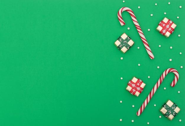 Świąteczna zieleń z dwoma cukierkami, pudełkami z czerwoną i zieloną wstążką i koralikami.