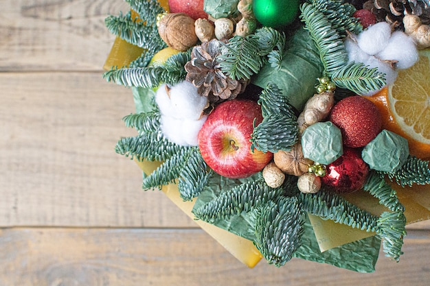 Świąteczna zimowa kompozycja kwiatowa z gałęziami drzew jabłkami cukierkami pomarańczową bawełną i orzechami