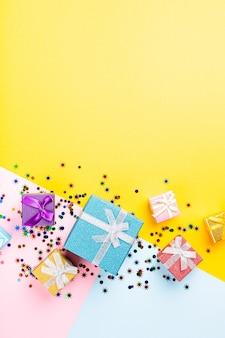 Świąteczna żółta powierzchnia z kolorowymi prezentami. koncepcja karty z pozdrowieniami na urodziny, boże narodzenie, karnawał. skopiuj miejsce, widok z góry, płaski układ