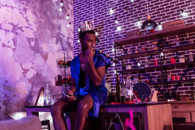 Świąteczne atrybuty. ciekawy afroamerykanin grający z gwizdkiem i noszący tekturową koronę