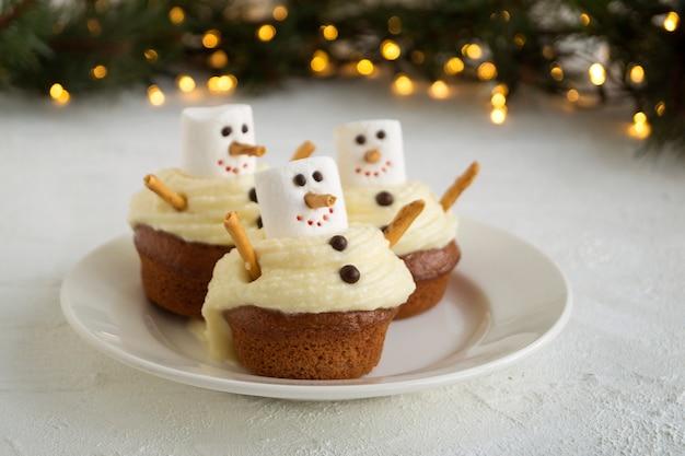 Świąteczne babeczki czekoladowe z wystrojem bałwana.