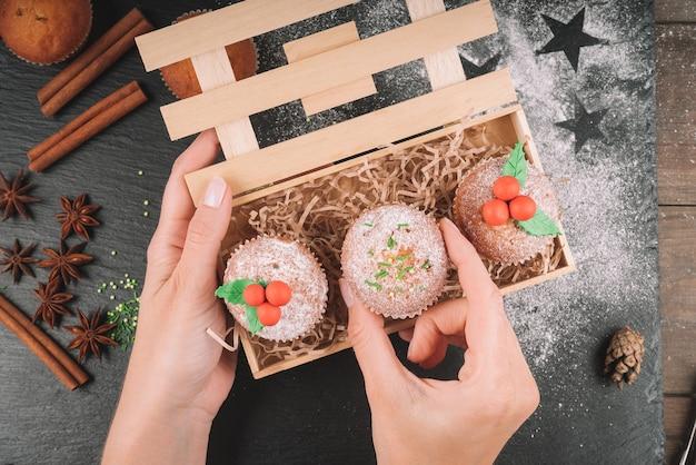 Świąteczne babeczki ozdobione jemiołą w drewnianym pudełku