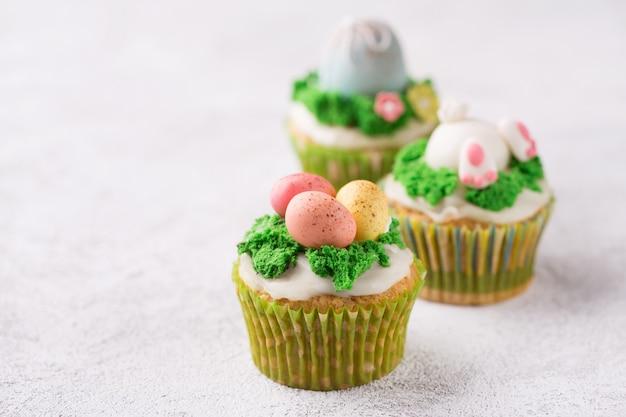 Świąteczne babeczki z mastyksowymi jajkami i trawą na jaskrawym tle. koncepcja świąt wielkanocnych. skopiuj miejsce