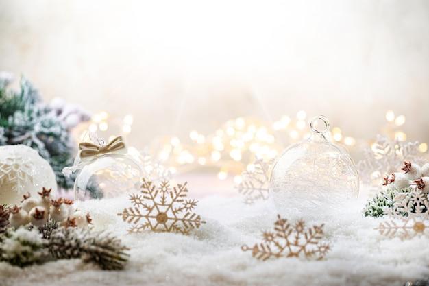 Świąteczne białe ozdoby na śniegu z gałęziami jodły i zimową dekoracją świątecznych świateł