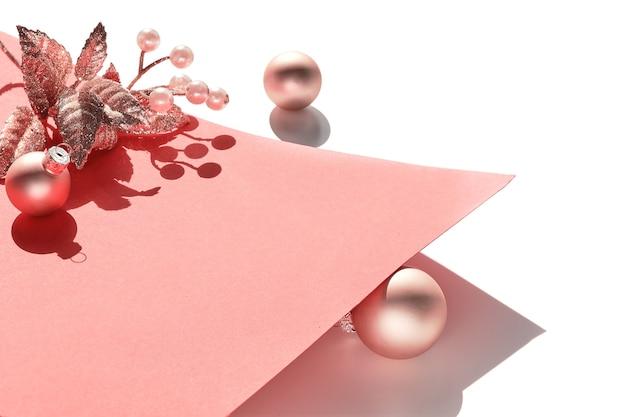 Świąteczne bibeloty, gałązka i jagoda na różowym papierze