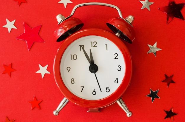 Świąteczne boże narodzenie z budzikiem w czerwonym minimalistycznym stylu.