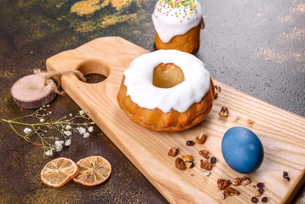 Świąteczne ciasta z białą polewą, orzechami i rodzynkami z pisankami na świątecznym stole. przygotowania do wielkanocy
