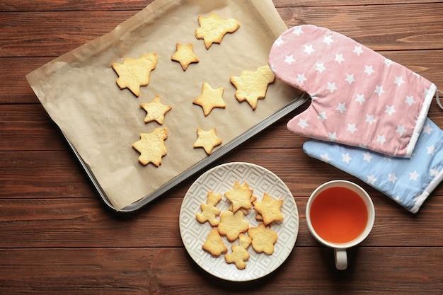 Świąteczne ciasteczka i filiżanka herbaty na drewnianym stole