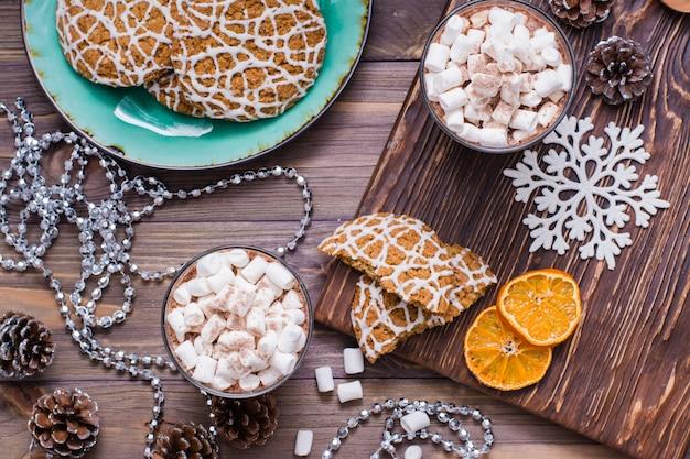 Świąteczne ciasteczka i gorące kakao z pianki w szklankach na stole z ozdób choinkowych. widok z góry