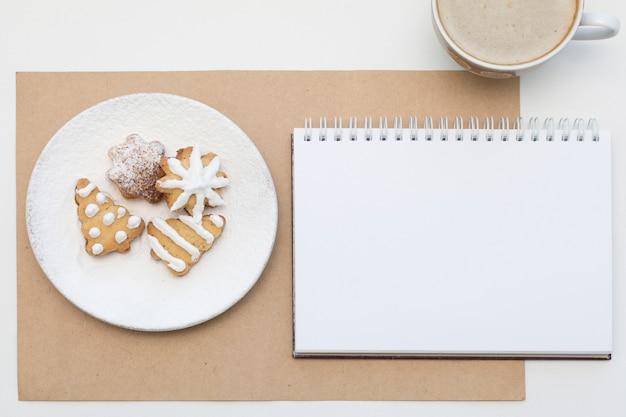 Świąteczne ciasteczka i pusty notatnik. makieta świątecznej kawy. widok z góry.