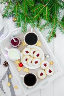Świąteczne ciasteczka linzer wypełnione dżemem truskawkowym na białym talerzu na tacy z dwiema filiżankami kawy.