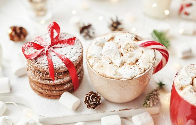 Świąteczne ciasteczka, mleko, kakao, pianki, cukierki na białym talerzu przy oknie
