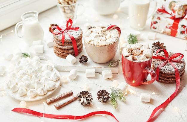 Świąteczne ciasteczka, mleko, kakao, pianki, talerz cukierków przy oknie