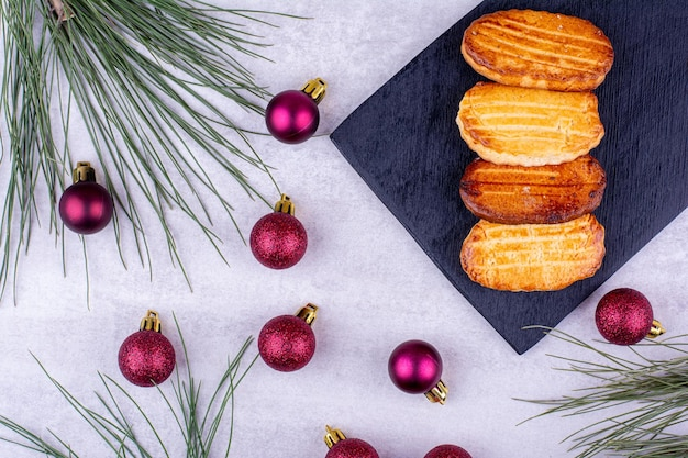 Świąteczne ciasteczka na czarnej płycie z bombkami. zdjęcie wysokiej jakości