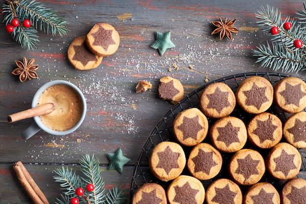 Świąteczne ciasteczka z czekoladową gwiazdą z espresso, przyprawami i dekorowanymi gałązkami jodły