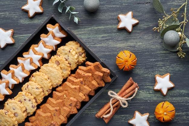 Świąteczne ciasteczka z kawałkami czekolady, płaskie leżały z przyprawami i zimowe dekoracje na ciemności