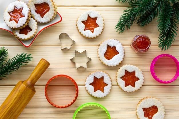 Świąteczne ciastka linzer z foremkami i wałkiem do ciasta na drewnianym stole