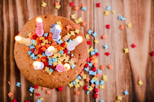 Świąteczne ciastko, posypane dekoracjami, z zapalonymi świecami