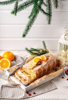 Świąteczne ciasto pomarańczowe z żurawiną i polewą cukrową na rustykalnym drewnianym tle