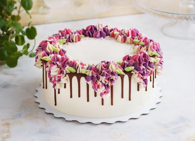 Świąteczne ciasto z kremowymi kwiatami hortensji na świetle