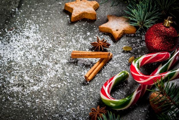 Świąteczne ciemności z gałęzi choinki, szyszek sosny, słodyczy z trzciny cukrowej, prezentów, bombek i dekoracji, copyspace