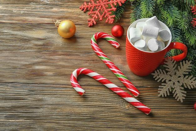 Świąteczne cukierki i filiżanka kakao z piankami na drewnianym stole