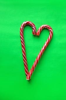 Świąteczne cukierki na zielonym prostym tle w formie serca po południu