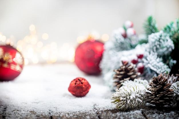 Świąteczne czerwone ozdoby na śniegu z gałęziami jodły i zimową dekoracją świątecznych świateł