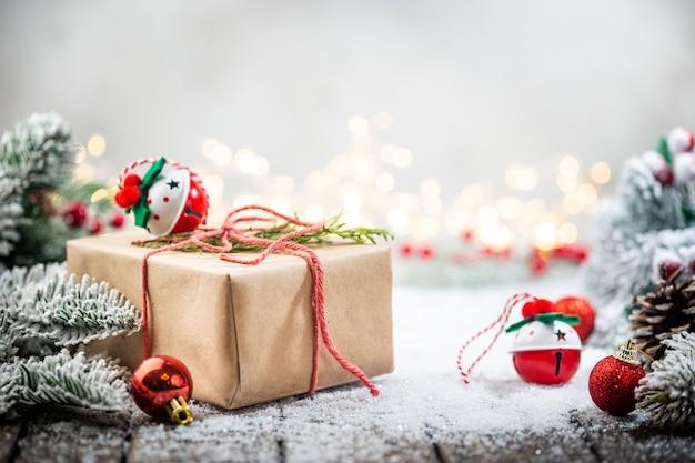 Świąteczne czerwone ozdoby na śniegu z pudełkami na prezenty gałęzie jodły i świąteczne lampki zimą