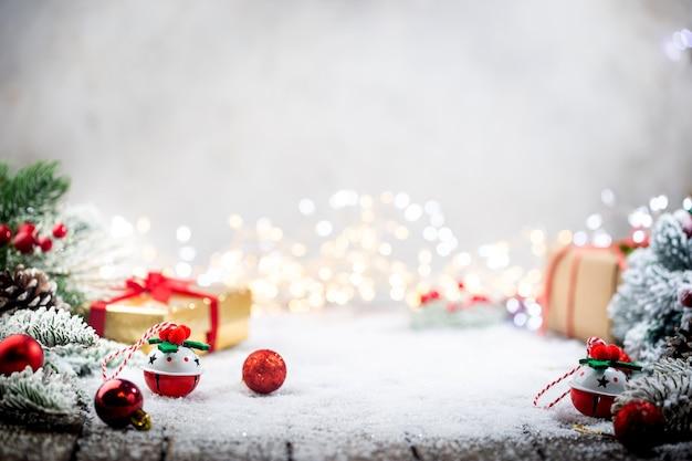 Świąteczne czerwone ozdoby na śniegu z pudełkami na prezenty z gałęziami jodły i lampkami bożonarodzeniowymi