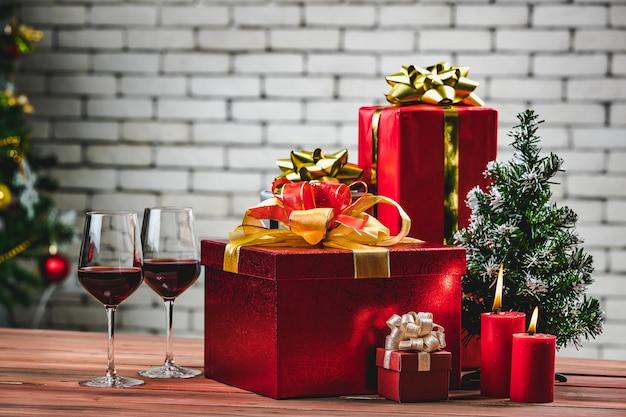 Świąteczne czerwone pudełko i czerwone rozjaśnić świece na pokładzie naturalnego drewna udekorować choinką, tło niewyraźne białe cegły ściany tło.
