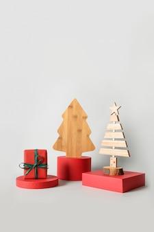Świąteczne czerwone stojaki z prezentem i dekoracyjną drewnianą kreatywną choinką