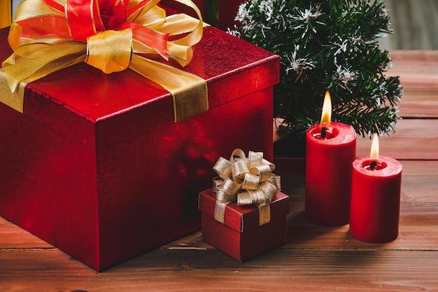 Świąteczne czerwone świece rozjaśniają się obok pięknych czerwonych pudełek na prezenty złotej wstążki ustawionej na naturalnej desce z drewna.