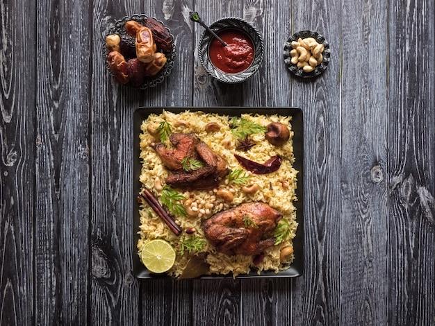 Świąteczne danie z pieczonym kurczakiem i ryżem. mandi kabsa, styl jemeński