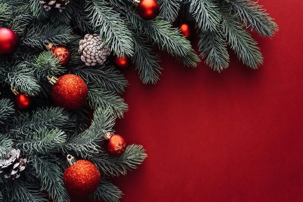 Świąteczne dekoracje czerwone, gałęzie jodły na czerwonym tle.
