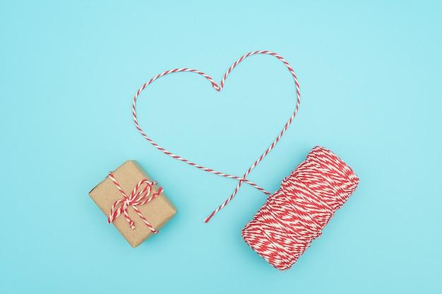 Świąteczne dekoracje czerwono-biały sznurek w kształcie serca i ozdobne pudełko. prezent na boże narodzenie koncepcja