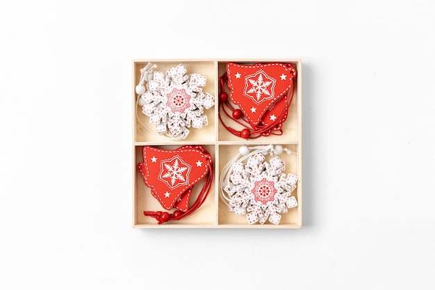 Świąteczne dekoracje drewniane pudełko z czerwonymi i białymi przedmiotami. widok z góry.