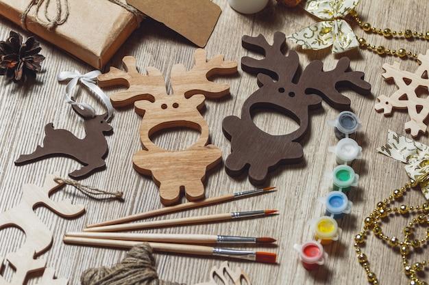 Świąteczne dekoracje drewniane, świąteczne jelenie, farby i pędzle