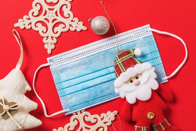 Świąteczne dekoracje i maska medyczna na czerwonym tle świąteczna kwarantanna z powodu pandemii covid19