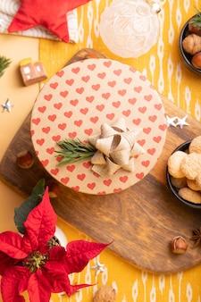 Świąteczne dekoracje na stole. flatlay z ozdobnym pudełkiem, poinsecją, orzechami, bombkami