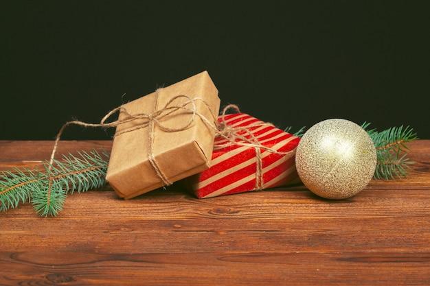 Świąteczne dekoracje, pudełko i gałęzie sosny na drewnianym tle
