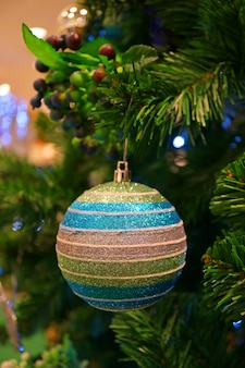 Świąteczne dekoracje sezonowe z wielokolorowym ornamentem w kształcie kuli na choince