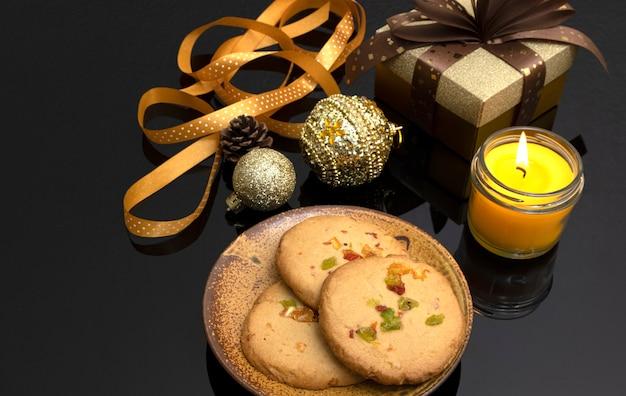 Świąteczne dekoracje stołu z ciasteczkami ze skórki pomarańczy, pudełkiem prezentowym i świecą zapachową.